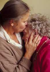 Mature daughter kissing her elderly mother